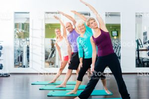 Group of senior people and young woman and men in fitness gym doing gymnastics